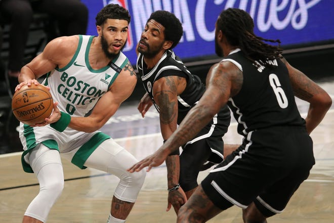Celtics small forward Jayson Tatum controls the ball while defended by Nets point guard Kyrie Irving, center, and center DeAndre Jordan during the first quarter of a game last month at the Barclays Center.