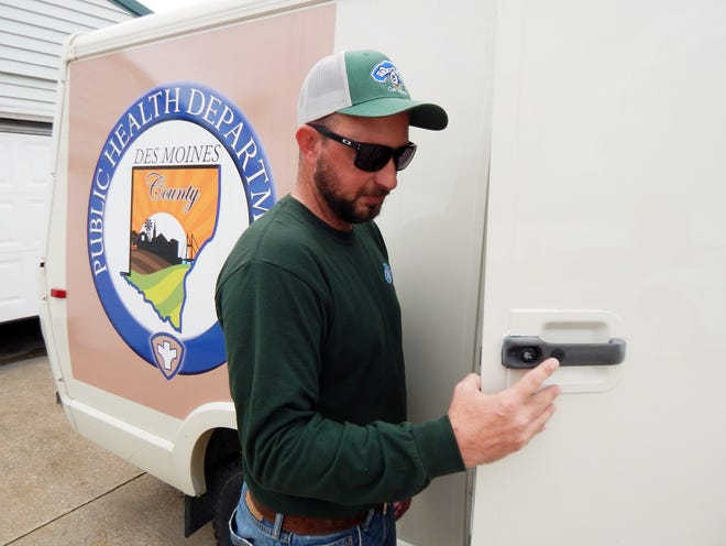 AJ Fesler of Water Works Car Wash, 500 S. Roosevelt Ave. in Burlington, inspects the new COVID-mobile — formerly the sheriff's department McGruff-mobile — Thursday after getting it ready for its inaugural appearance at Farmers Market Thursday. The portable vaccine clinic will be parked from 4 to 7 p.m. at 500 Jefferson St.