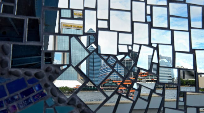 """The downtown skyline is reflected in the mirror tiles of the Roux Art mosaic """"Mirrored River: Where do you see yourself?"""" installed under the Main Street Bridge along the Southbank Riverwalk."""