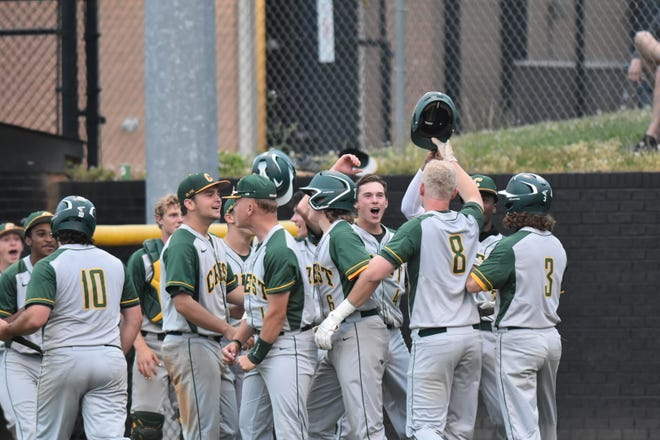 Crest's Luke Reynolds (8) is welcomed at home plate by teammates after hitting a home run at Kings Mountain.