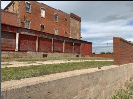 This photo shows the unused lot that once served as a loading area and most of the seven garage doors that will be removed and framed in as part of a remodel planned by owners of the Stevens Building, 225 S. Main. The corrugated metal on the wall to the right of the doors will also be replaced.