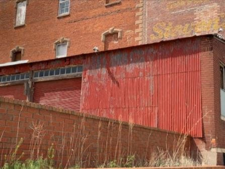 This photo shows the panel of corrugated metal that owners of the Stevens Building are proposing to replace with more significant metal siding, as well as some of the garage doors they want to eliminate.