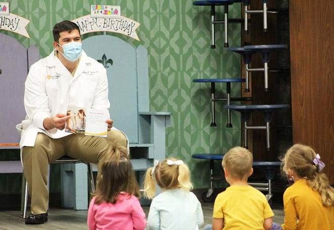"""In celebration of National Hospital Week, Zing Zumm Children's Museum recently hosted Naval Medical Center Camp Lejeune's Trauma Director, Lt. Cmdr. Douglas Pokorny as a guest story reader during storytime at the museum. Dr. Pokorny selected """"Doctors Help"""" by Dee Ready to read. NMCCL participates in the Reach Out and Read which provides children with books during milestone visits. Physicians work with the child and parents on reading aloud to build family connections."""