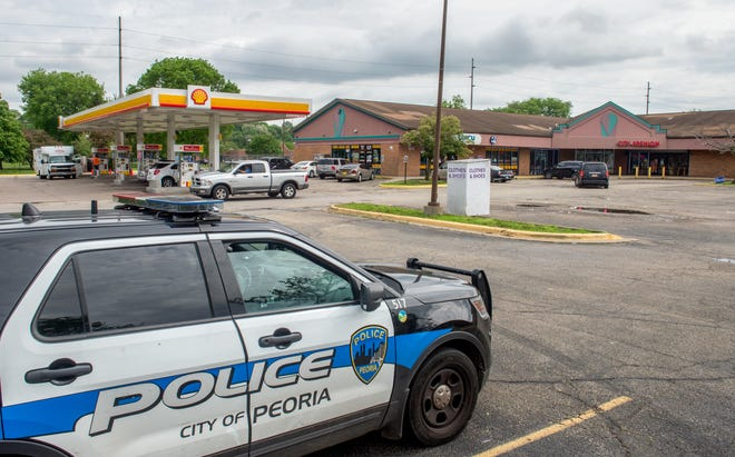 A Peoria police officer keeps watch Wednesday, May 19, 2021, in the parking lot at the Valley Park Shopping Center on MacArthur Highway in Peoria.