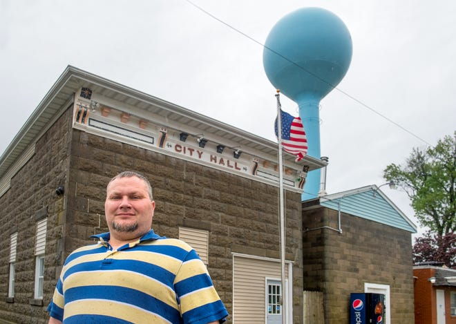 Village President Eric Boesdorfer stands in front of City Hall next to the water tower in Armington. The village south of Minier won't be able to afford its lone police officer anymore because of new, higher fees Tazewell County is charging for improved 911 service.