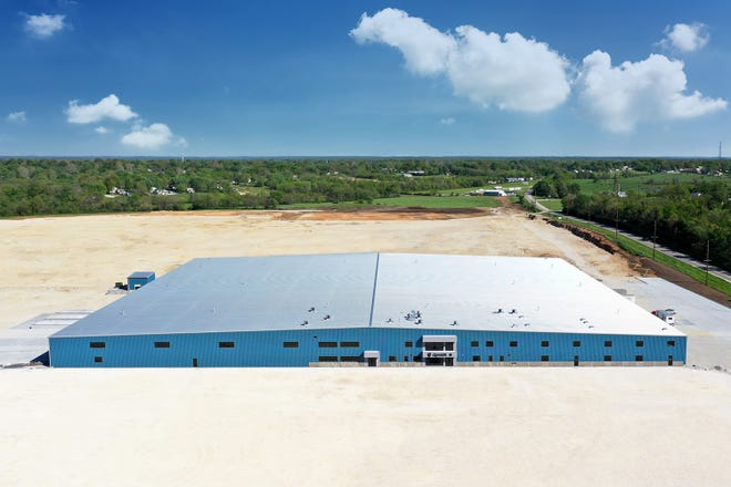 An aerial view of the Quaker Windows plant in Eldon and the plot of empty, leveled land that will be the site of their new expansion.