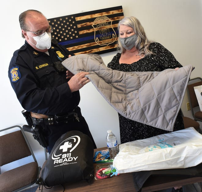 Carleton Police Chief Roy Johnson takes a look at the weighted blanket used to reduce anxiety for autistic children. The blanket is part of the autistic 911 Ready bag produced by Founder and President of Mimi's Mission Lisa Vilella of Woodhaven. Also in the bag are head phones, fidgets toys, bag of cookies and water to help autistic children relax if police have to arrive on a scene.