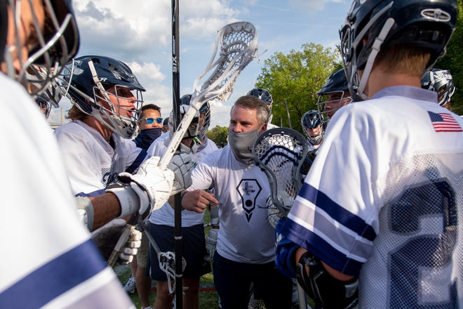 Framingham head coach AJ Mulvey revs up the team in between periods of the game against Newton North at Phil Read Field in Framingham, May 18, 2021. The Tigers beat the Flyers, 10-9.