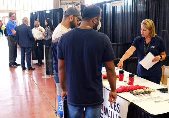 Two men stop at the Capital Distributing booth during a May job fair in the Centennial building at the OKC Fairgrounds.