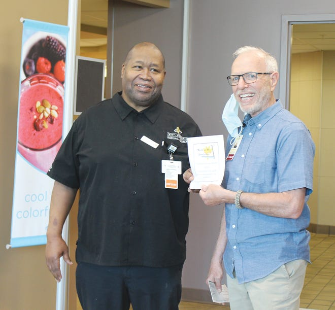 Marvin Blake accepts a certificate for Faithful Servant Award from PRMC Faith in the Workplace committe member Ron Moser on Wednesday, May 12, 2021 in Pratt.