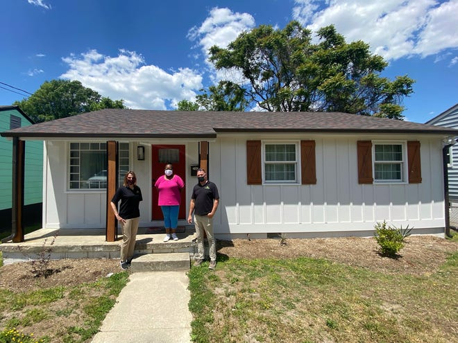 Angela Wilson, Pastor Gary McReynolds, and his wife Tracy, outside the newly revitalized Cameron Street home in the Blandford neighborhood.