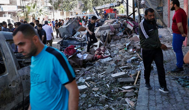 People inspect the rubble of the destroyed Abu Hussein building in Gaza City, which was hit by an Israeli airstrike early Wednesday.