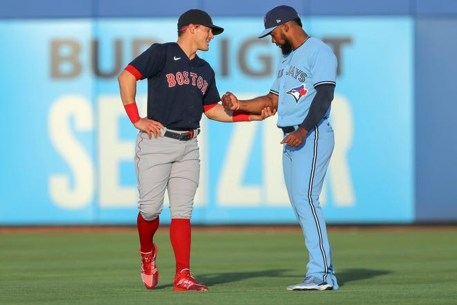 Boston Red Sox's Enrique Hernández, left, talks with Toronto Blue Jays' Teoscar Hernandez prior to a baseball game Tuesday, May 18, 2021, in Dunedin, Fla. (AP Photo/Mike Carlson) ORG XMIT: FLMC102