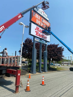 Tim O'Dowd, up in the lift, and Rick Novella, left, install a new Market Basket sign Wednesday afternoon on Bald Hill Road in Warwick. They are from Barlo Signs, in Hudson, NH.