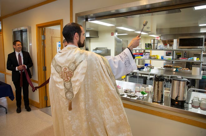 Joined by Todd Salnas, chief executive of PeaceHealth Oregon, left, the Rev. Mark Bentz of St. Alice Catholic Church blesses the new kitchen during a ribbon-cutting ceremony at the Springfield parish.