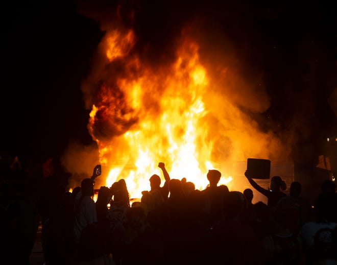 Protesters gather around a fire they set in the middle West 7th Ave. at Washington Street. in Eugene in protest over the killing of George Floyd in  Minneapolis, Minnesota on May 29, 2020.
