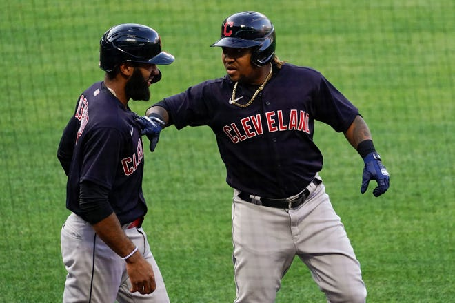 Cleveland's Jose Ramirez, right, celebrates with Amed Rosario, left, after they both scored off of a home run hit by Ramirez during the first inning against the Los Angeles Angels Tuesday, May 18, 2021, in Anaheim. (AP Photo/Ashley Landis)