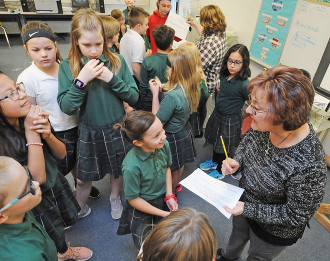 Shirley Zink, St. Mary's 4th grade teacher, acts as a judge as she checks over one group's arrest warrant during the mock crime scene investigation set up by Jessica Patterson, Evidence Technician for the Salina Police Department, at St. Mary's Grade School in Salina in 2019. St. Mary's Grade School will be having summer programs throughout the entire summer.