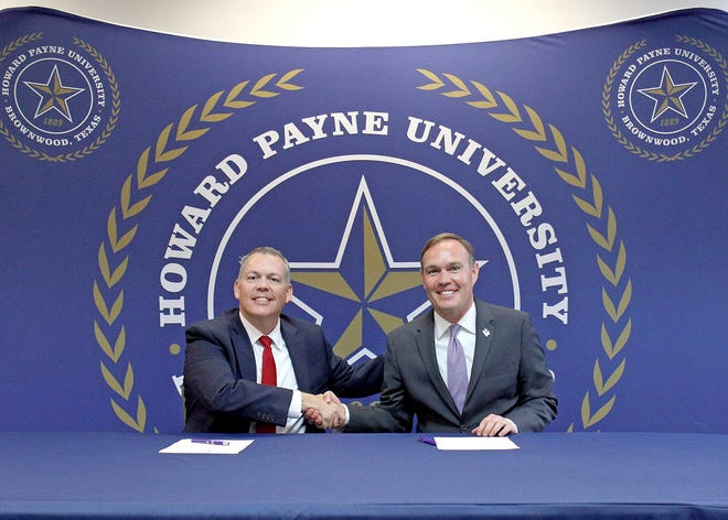 Tarleton State University President Dr. James Hurley, right, and Howard Payne University President Dr. Cory Hines, shake hands after signing a Memorandum of Understanding allowing easier transition for high-achieving HPU students to Tarleton's masters of environmental science program.
