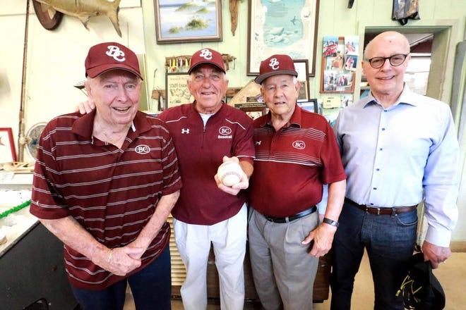 Charlie Russo holds a ball autographed by current senior pitcher Carter Holton as he stands with with some of his Benedictine teammates from the 1961 state championship baseball team: Denny Herb (left), Stan Friedman (right) and coach Charlie Moore.
