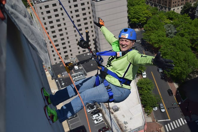 """Mary Ann Evans, of Smyrna, rappelled 17 stories down the side of the 300 Delaware Ave. building in Wilmington on May 13 to support Special Olympics Delaware. Evans is one of just 10 """"edgers"""" to participate all 10 years the event has been held."""