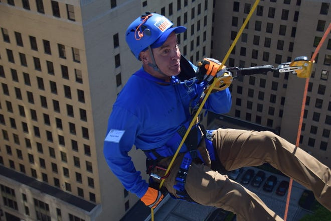 """Danny Hall, of Clayton, rappelled 17 stories down the side of the 300 Delaware Ave. building in Wilmington on May 13 to support Special Olympics Delaware. Hall is one of just 10 """"edgers"""" to participate all 10 years the event has been held."""