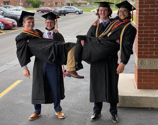 Calvin DeSplinter and Kevin VanWassenhove clown around before the graduation ceremony by giving Gabe Johnson and Connor Bryan a lift.