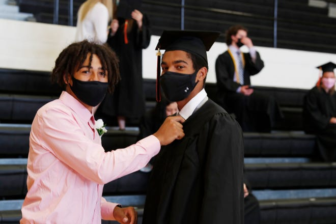 Denniko Powe takes time to help adjust Melcon DeJesus III necktie before making the walk to get his diploma at Kewanee High School Stadium. It was the first outdoors graduation held at KHS since the 1980s.