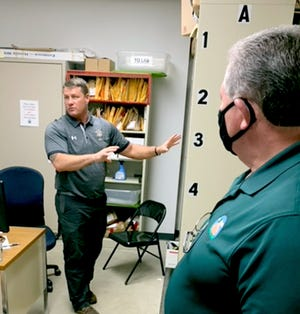 Sheriff Mark Lillywhite explains to county commissioners, including Ken Malone, the process of documenting evidence at the sheriff's department. At Lillywhite's request, commissioners toured the department and the jail Tuesday.
