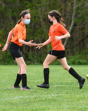 Kaylee Roche and Hadley Goyette, members of the Middleboro Youth Soccer Association 5th and 6th grade team, celebrate a goal during a win over Plymouth in Coastal Leauge play.
