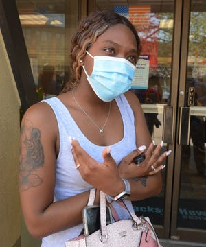 Dominique Hyppolite, of Groton, wears her mask in downtown Norwich Wednesday on the first day Connecticut residents do not have to wear them outside.
