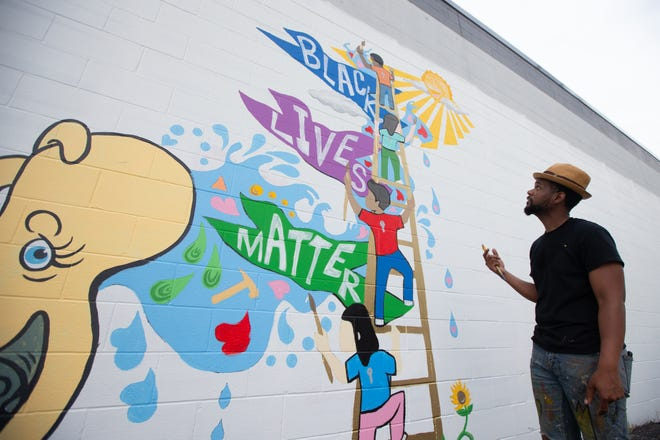 Artist Jordan Brooks stands next to his latest installation of a mural just east of Redbud Park in NOTO.