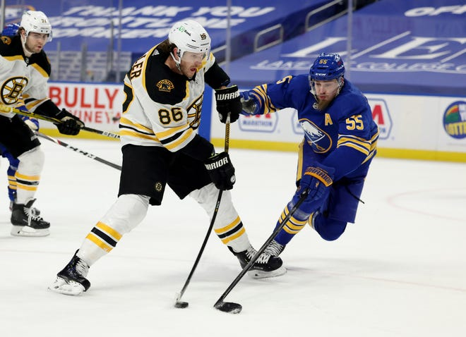 Bruins defenseman Kevan Miller takes a shot during a game last month in Buffalo, while Sabres defenseman Rasmus Ristolainen tries to block it.