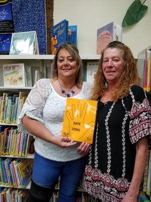 Diana Smith and Donna Moody hold a Safe Zone sign that shows children a place where they can find a trusted adult. Moody is the Director of the Claymont Public Library. Libraries in Uhrichsville and Dennison are safe zones for children. Smith is a drug abuse prevention educator.