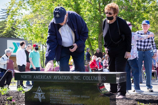 David Roscoe of Columbus, a 51-year employee at North American Aviation and Rockwell International, and his wife, Lavonne, look at the memorial bench dedicated May 15 to the Columbus airplane manufacturing plant, its employees and their families. The granite bench in Whitehall Community Park is festooned with images of historic aircraft built there. About 100 people gathered at the park for the dedication.