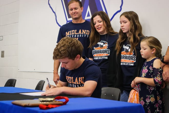 Austin Cuthbertson, surrounded by family members signed to Powerlift for Midland University.