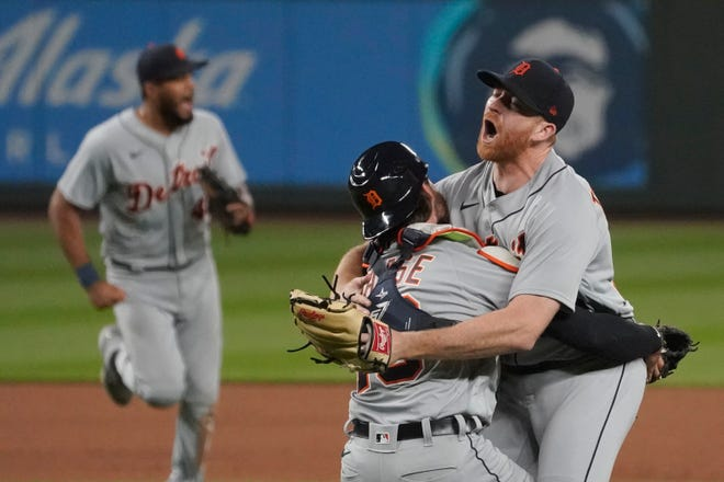 Detroit Tigers starting pitcher Spencer Turnbull, right, hugs catcher Eric Haase as teammates rush in after Turnbull threw a no-hitter in a baseball game against the Seattle Mariners, Tuesday, May 18, 2021, in Seattle. The Tigers won 5-0. (AP Photo/Ted S. Warren)