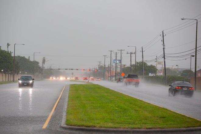 Cars drive down Saratoga Boulevard in Corpus Christi as heavy rain falls on Wednesday, May 19, 2021.