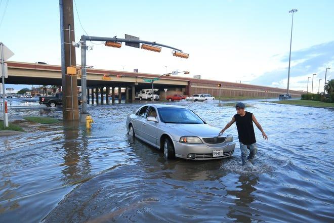 Steven Galindo walks around his car, which was flooded on Kostoryz Road on Monday, May 16, 2016.