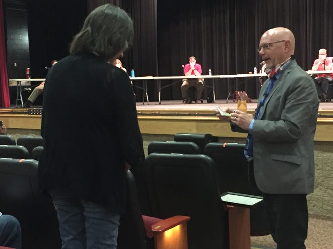 Shelby Superintendent Tim Tarvin presents retiring teacher Linda Durkin with her retirement gift at Tuesday's school board meeting.