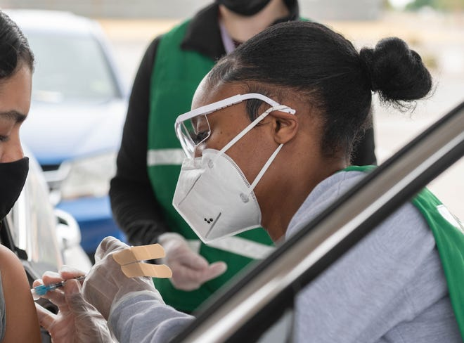 Eriell Wallace, a nursing student at New Mexico State University, administers a COVID-19 vaccine during a clinic at NMSU on April 30.