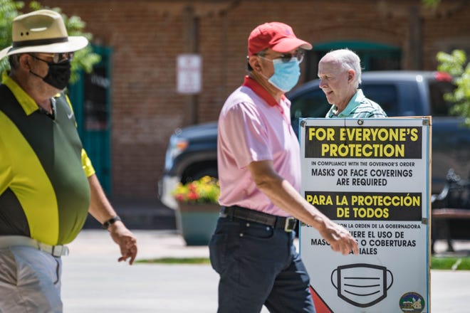 Some visiting the Mesilla Plaza on Wednesday, May 19, 2021, wear masks while others do not. The town has signs referencing mask wearing per the governor's orders. Last week, New Mexico issued guidance stating people who were vaccinated could go maskless in most settings.