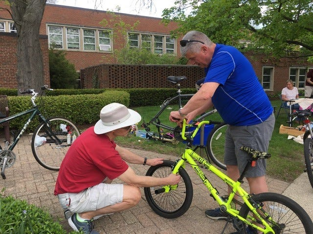 Ken Swarthout (left) and David Trippett  work to repair the brakes on a child sized bicycle which a happy child will receive along with a lock and helmet and safety instruction.