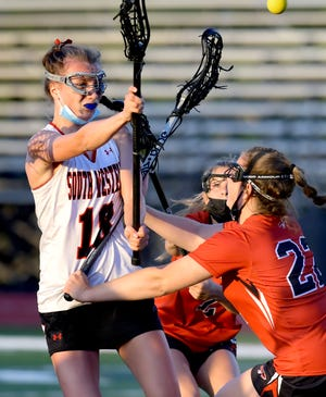 South Western's Leah Leonard takes a shot over Warwick's Leah McKay in a District 3 Class 3-A girls' lacrosse match at South Western Tuesday, May 18, 2021. Bill Kalina photo