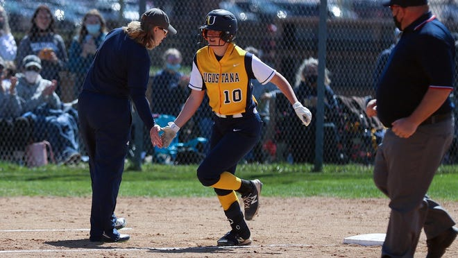 Augustana's Torri Chute (10) is congratulated by coach Gretta Melsted as she rounds third base after a home run.