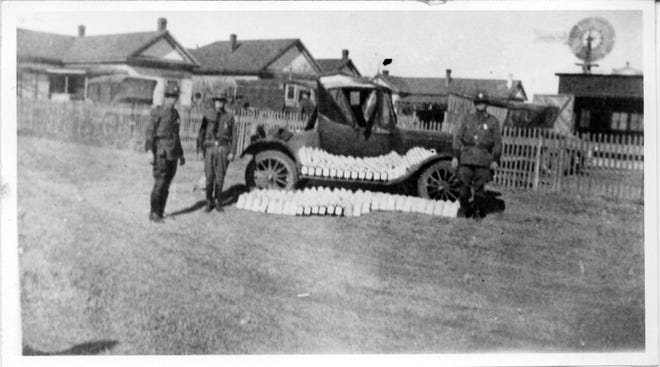 Photograph of three U.S. Border Patrolmen standing by their vehicle at headquarters in Marfa, Texas. Bottles of liquor, confiscated during Prohibition, are displayed in the photo.