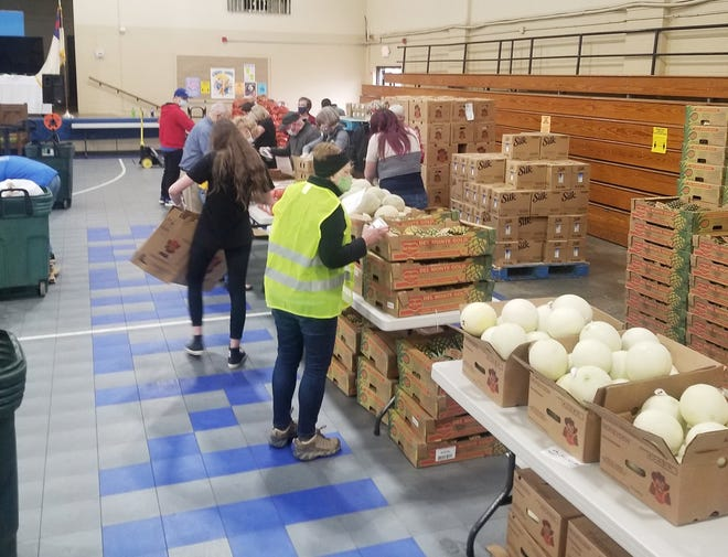 Volunteers load carts with fresh produce during the Eastside Community Ministries fresh produce giveaway at First Baptist Church in Zanesville in March.