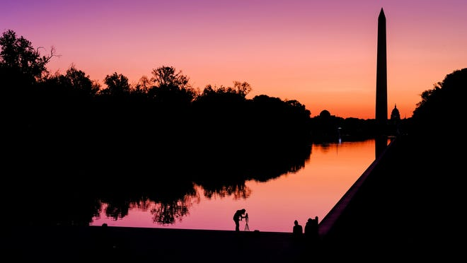 In this Sept. 21, 2019, file photo, a photographer lines up her shot at the National Mall reflecting pool as the sun begins to rise behind the Washington Monument and the U.S. Capitol building in Washington.