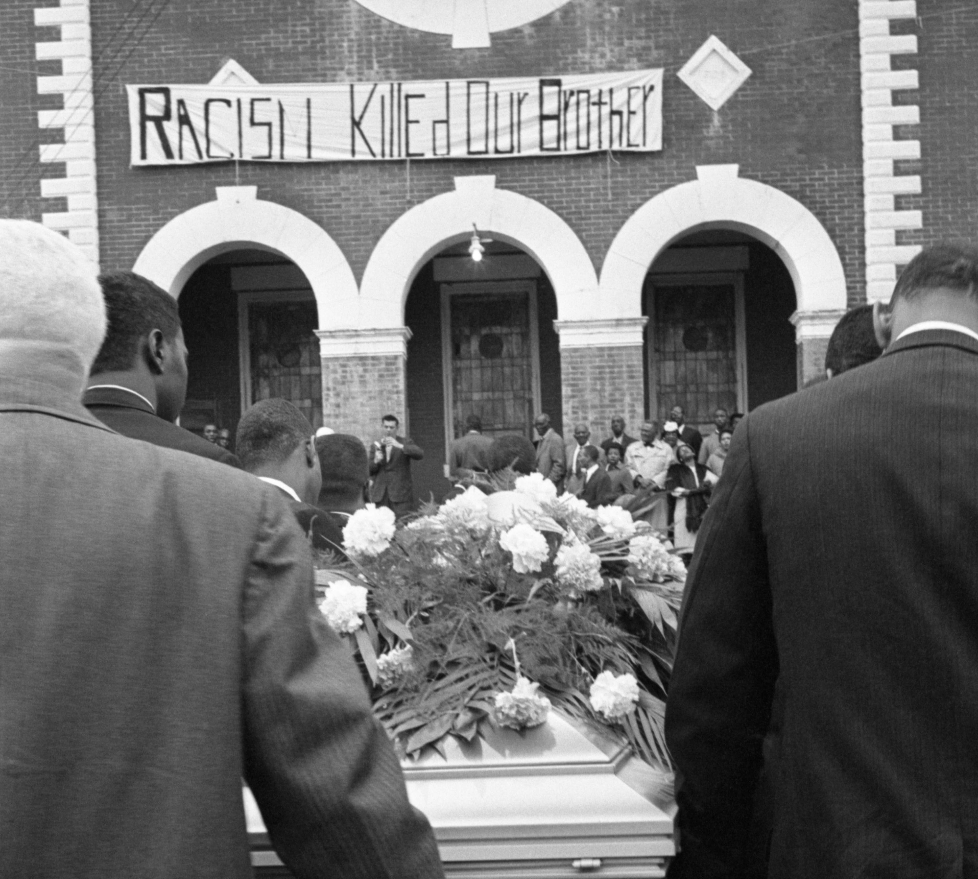 """The casket bearing the body of Jimmie Lee Jackson is carried into a church in Selma, Alabama for funeral services on March 3, 1965. A sign in front of the church reads, """"Racism Killed Our Brother."""""""