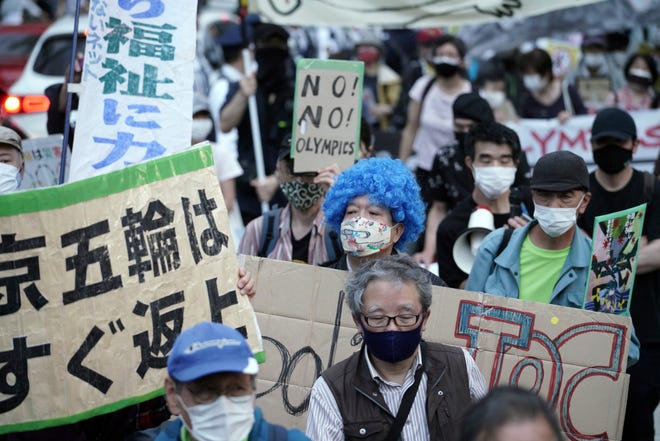 People who are against the Tokyo 2020 Olympics set to open in July, march to protest around Tokyo's National Stadium during an anti-Olympics demonstration Sunday, May 9, 2021.